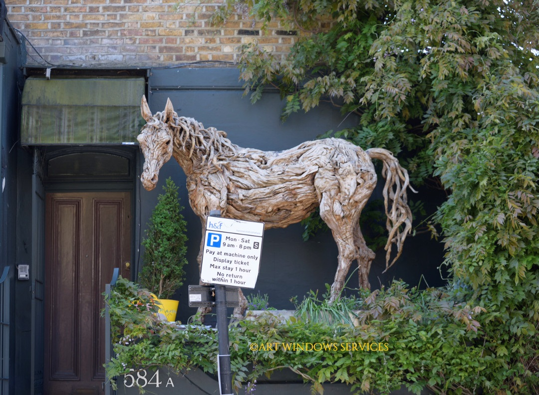 A door and a horse. Living sculpture of the horse found at Fulham